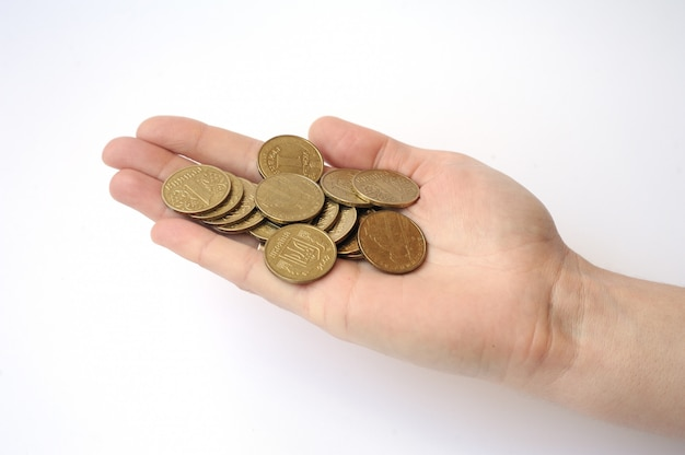 Hand on a white background holding a handful of coins one hryvni