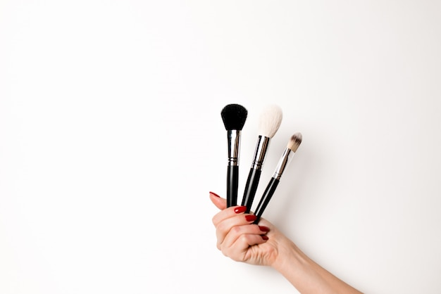 Hand on a white background keeps makeup brushes