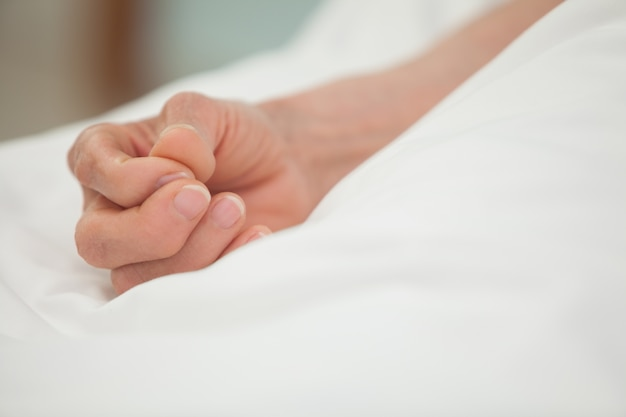 Hand in white bed cover