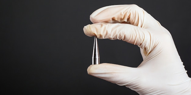 Hand in a white disposable glove holding a piercing ear expander for tunnel ear jewelry close-up.