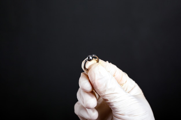 Hand in white glove holds piercing earring silver color on a dark background