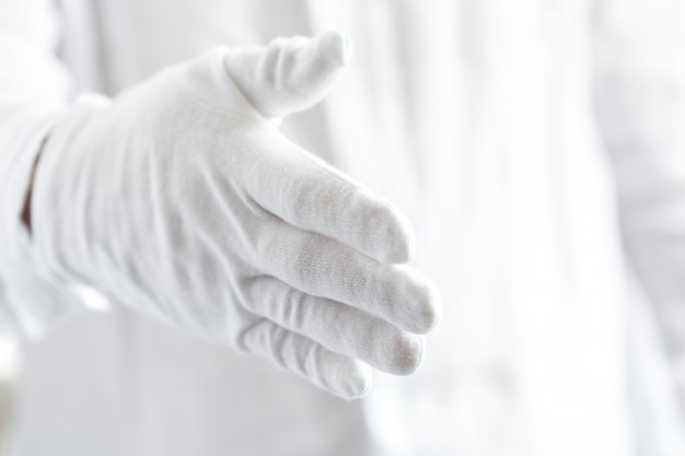 A hand in white glove is ready to shake