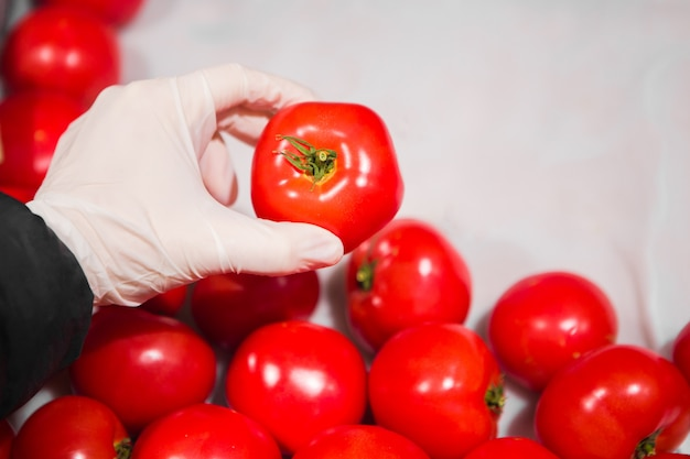 Hand in a white glove takes red tomato in a store. epidemic safety