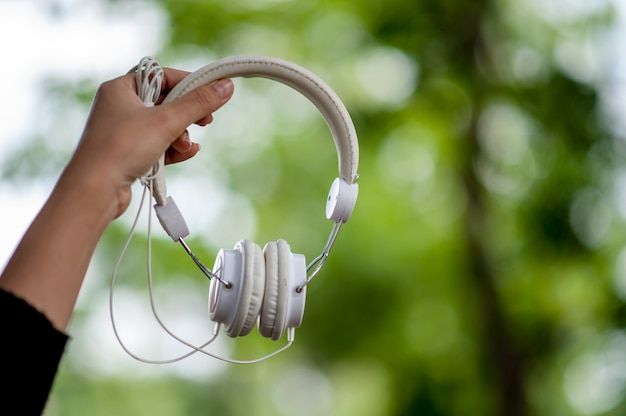 Hand and white headphones, devices for listening to music