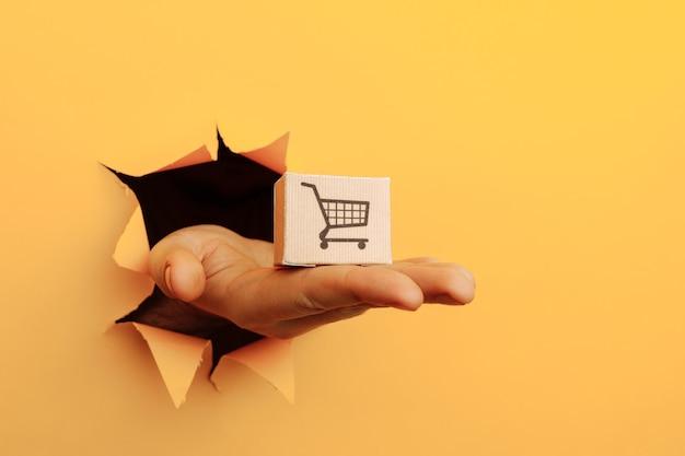 노란색 종이 구멍을 통해 상자와 손.