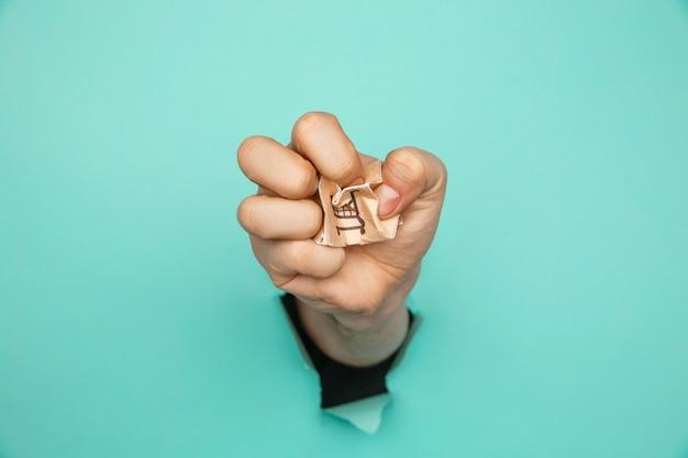 Рука со сломанной коробкой для доставки через синюю бумажную дырочку. авария отгрузки.
