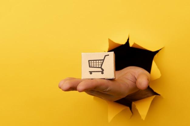 노란색 종이 구멍 배달 개념을 통해 배달 상자와 손