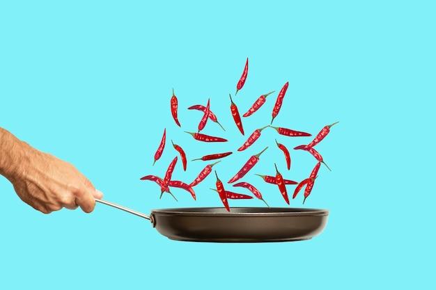 Рука со сковородой и острым перцем чили на цветном синем фоне еды