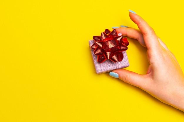텍스트를 위한 노란색 배경 박싱 데이 아이디어 공간에 선물 상자를 든 손