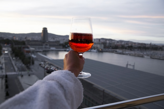 Рука с бокалом красного вина. вид на город