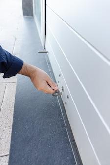Рука с ключом закрытие двери рольставни магазина. концепция закрытия