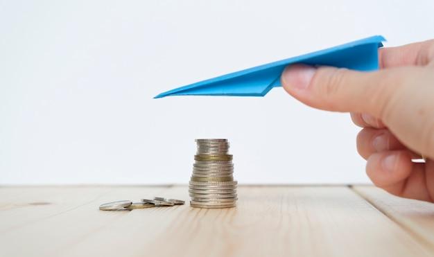 동전 더미 위에 종이 비행기로 손을. 소득 감소 개념입니다.