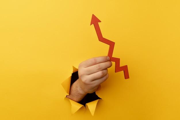 黄色い紙の穴から赤い矢印を上に向けて手渡します。ビジネスの成長の概念。
