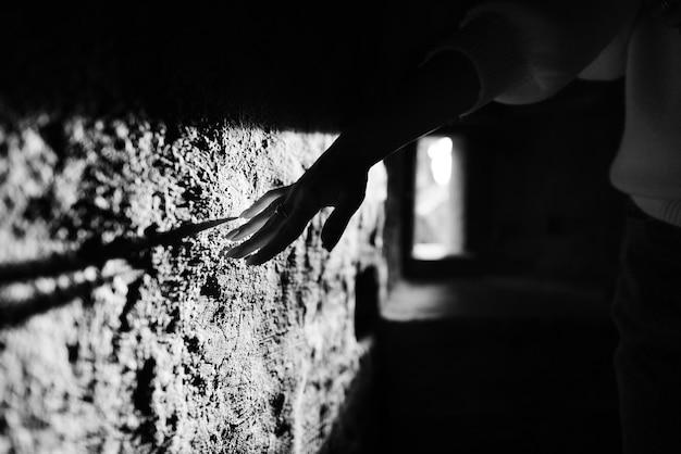벽 배경에 반지가 있는 손 세련된 흑백 사진
