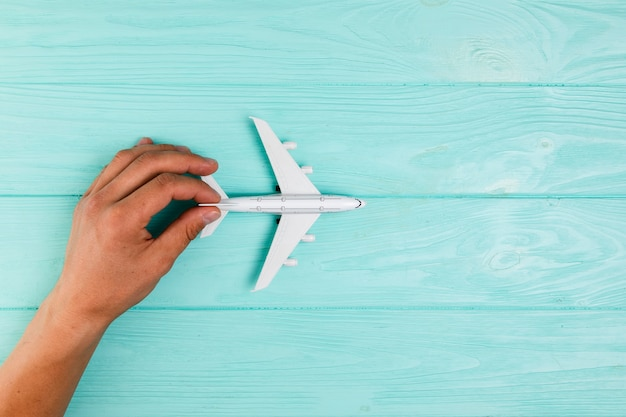 Hand with airplane toy on turquoise