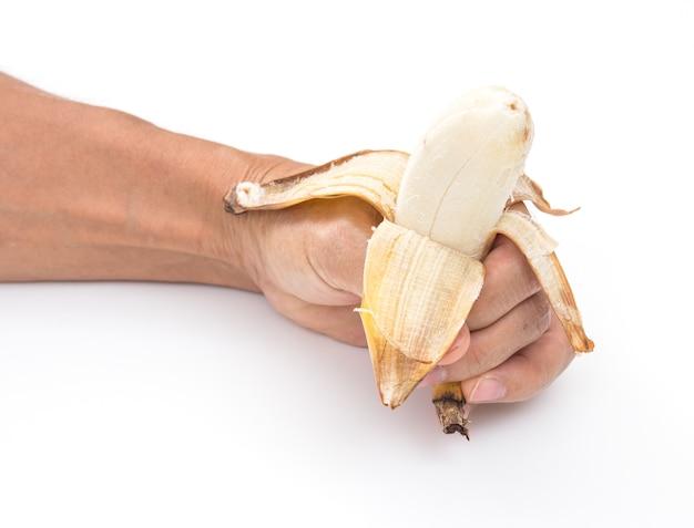 Рука с бананом на белом фоне