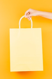 Hand with beige shopping packet
