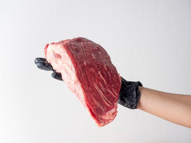 A hand with a black glove holds a piece of fresh raw marbled beef on a light background