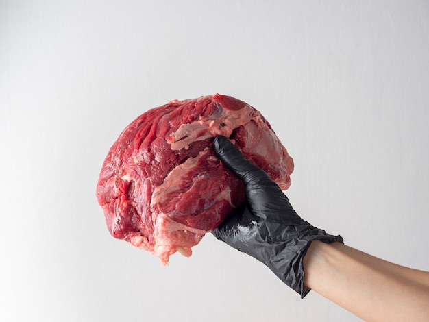 A hand with a black glove holds a piece of fresh raw marbled beef on a light wall