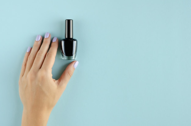 Hand with black nail polish composition on blue background.