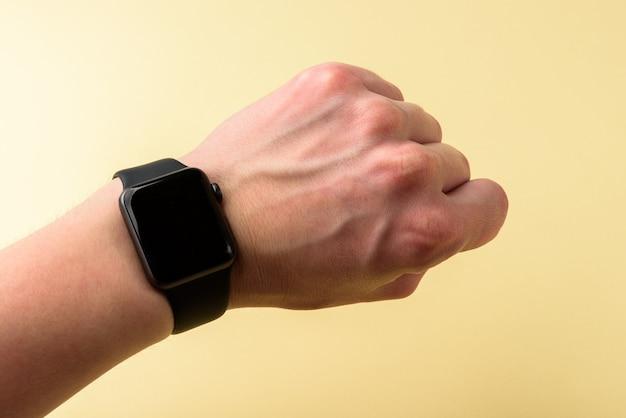노란색 바탕에 검은색 smartwatch와 손입니다.
