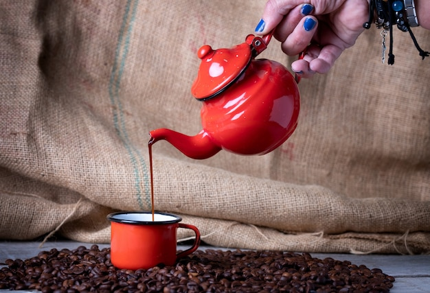 Hand with blue nails with red metal teapot making coffee in red metal cup