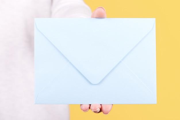 Рука с синим бумажным конвертом изолированы