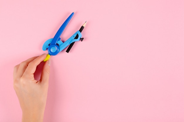 Hand with blue stationery compass for kids on pink background.