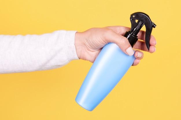 Рука с синей солнцезащитной бутылкой с распылителем изолирована