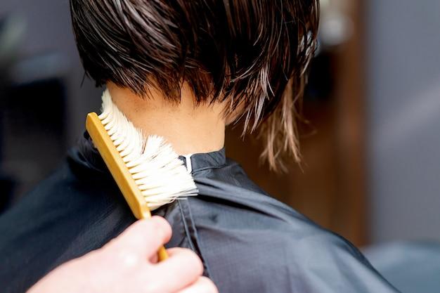 Рука с щеткой, очищающей шею женщины от стриженных волос заделывают.