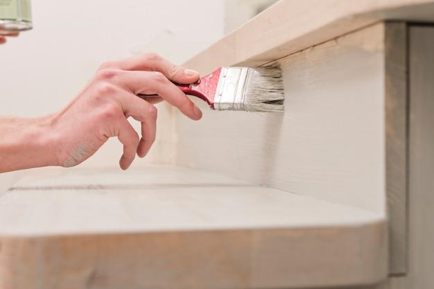 Рука с кисточкой для малярных работ