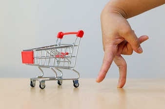 Hand with cart on wooden table.