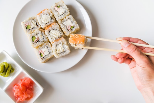 Hand with chopsticks grabbing a sushi roll