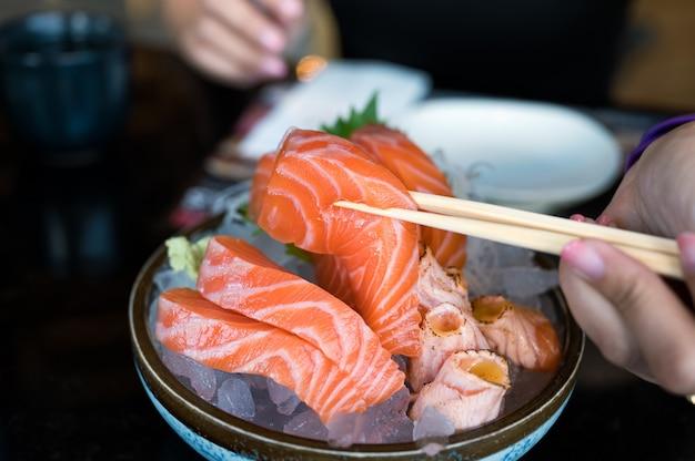 Рука с палочками для еды держит нарезанный сашими лосось на миске в японском ресторане