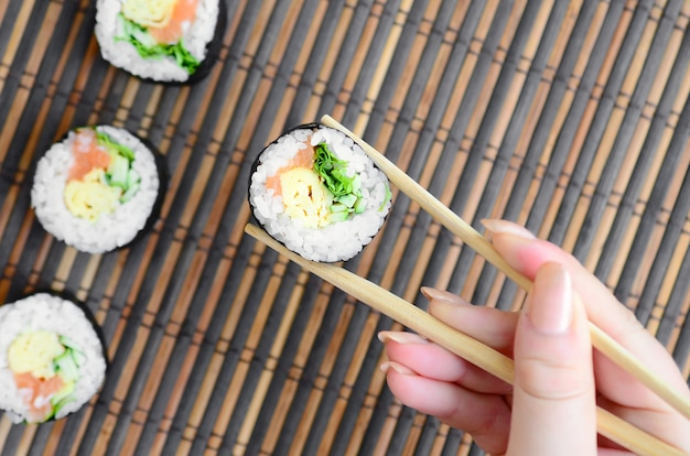 A hand with chopsticks holds a sushi roll on a bamboo straw serving mat