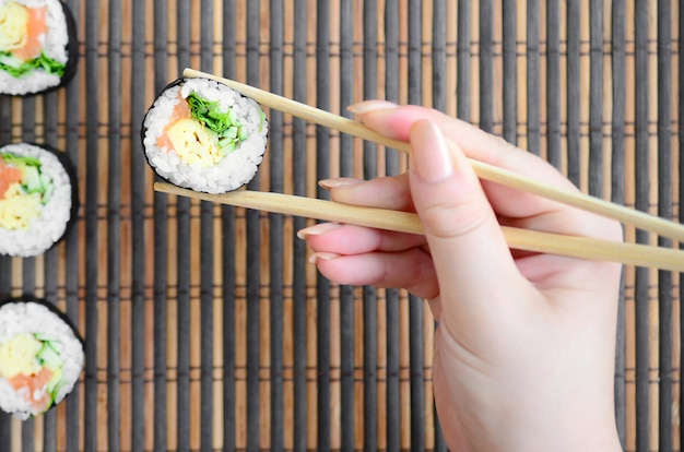 A hand with chopsticks holds a sushi roll on a bamboo straw serwing mat background