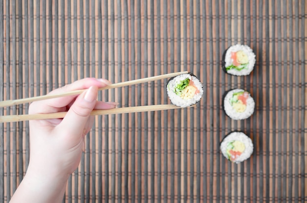 A hand with chopsticks holds a sushi roll on a bamboo straw serwing mat wall. traditional asian food.