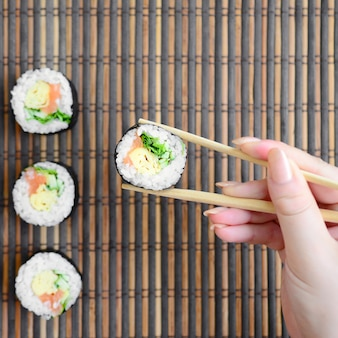 A hand with chopsticks holds a sushi roll on a bamboo straw serwing mat