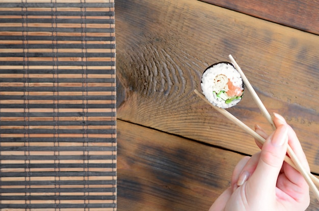 A hand with chopsticks holds a sushi roll on a bamboo straw
