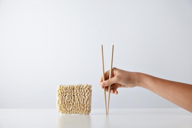 Рука с палочками для еды возле пакета прессованной сухой яичной лапши, изолированной на белом