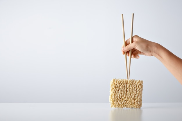 Hand with chopsticks above pack of pressed dry egg noodles isolated on white