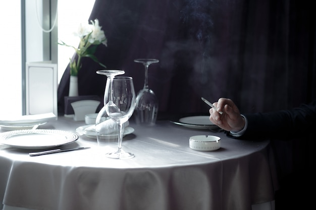 灰皿でタバコを持つ手をクローズアップ