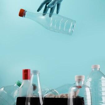 사용 된 플라스틱 병을 휴지통에 버리는 청소 장갑으로 손. 재사용, 재활용 및 폐기물 제로 캠페인 개념. 환경 관리