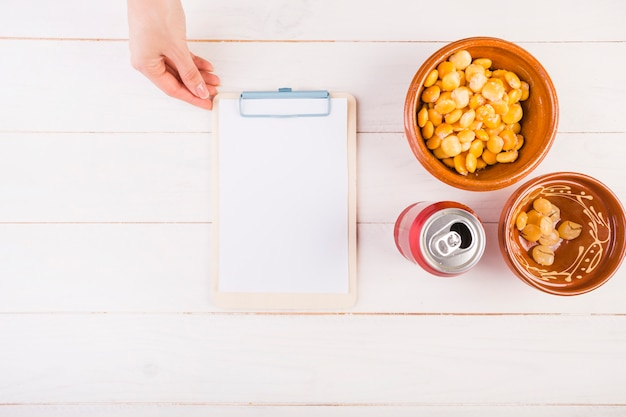 Hand with clipboard and bean snack on table