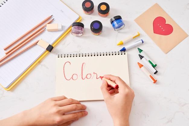 白いテーブルに色鉛筆と白紙の紙を持つ手
