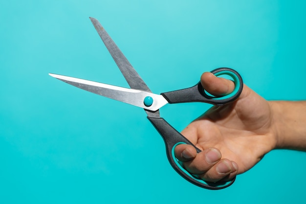 Hand with colorful pair of scissors in front of a blue background with copy space for text