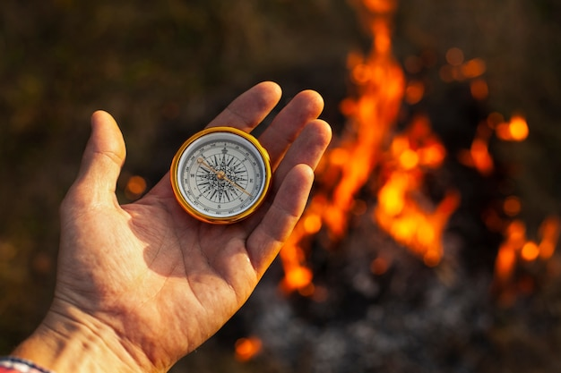 Hand with compass and fire flames along