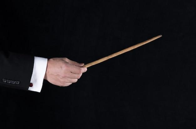 Рука с дирижерской дубинкой на черном фоне