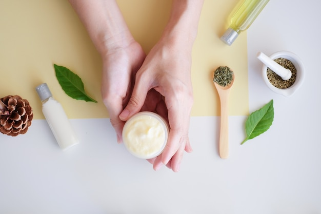 Hand with cream and natural ingredients.