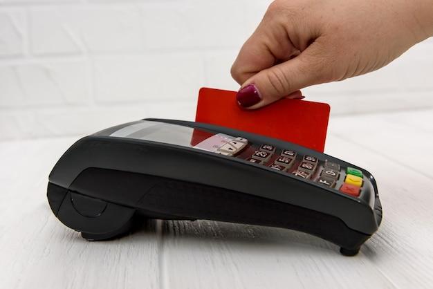 クレジットカードと銀行端末を持って手